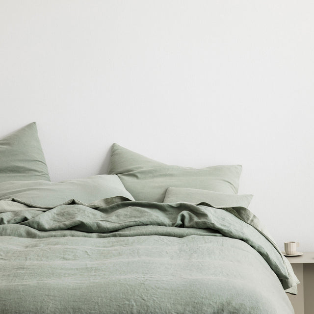 Bed styled with Sage Duvet Cover Set and Sage Sheet Set. On the bedside table is a small coffee cup.