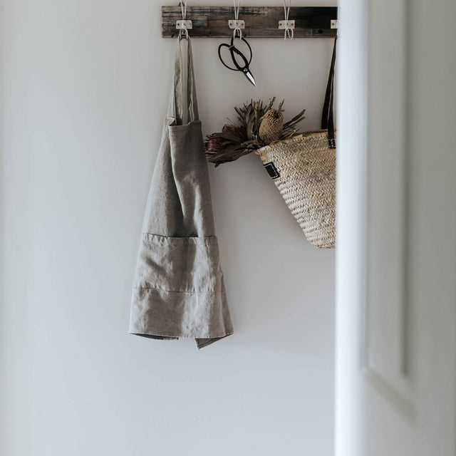 Jude Linen Apron in Natural color hangs on wall