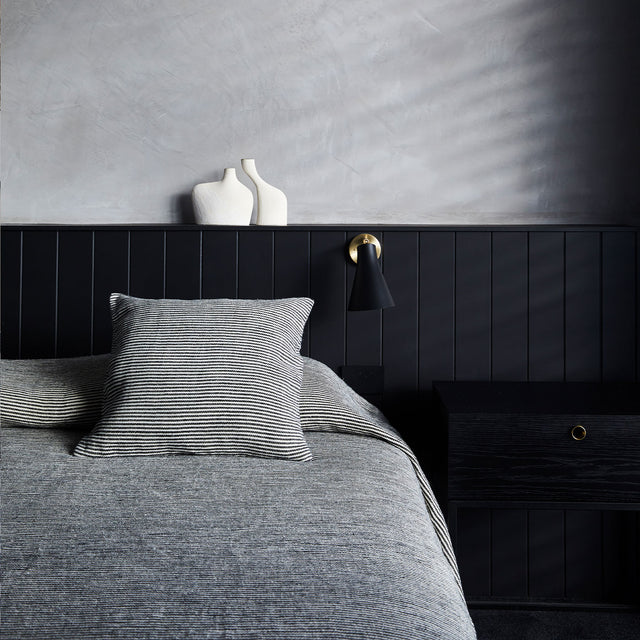 A bed in front of a black panelled wall. The bed is styled with the Mira Linen Bedcover and Mira Linen Cushion Cover in Ellis Stripe.