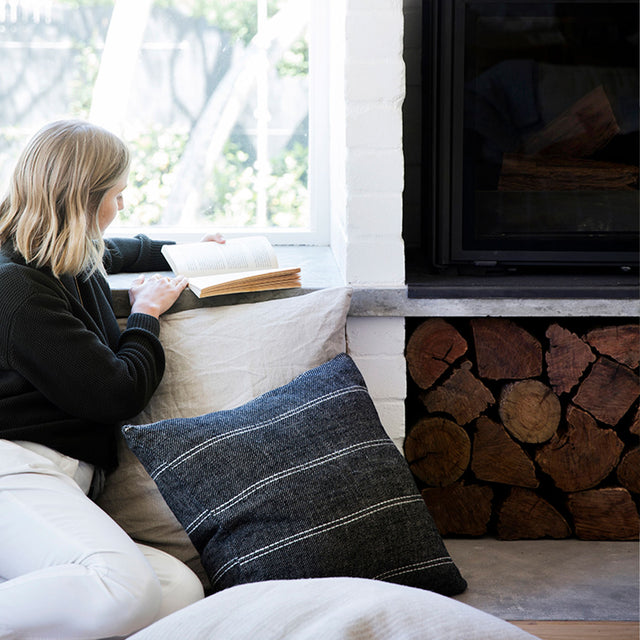 A model is sitting in front of a fireplace next to a window reading a book. She is wearing a black jumper and white pants. Next to her is the Mira Linen Cushion Cover in Rafa.