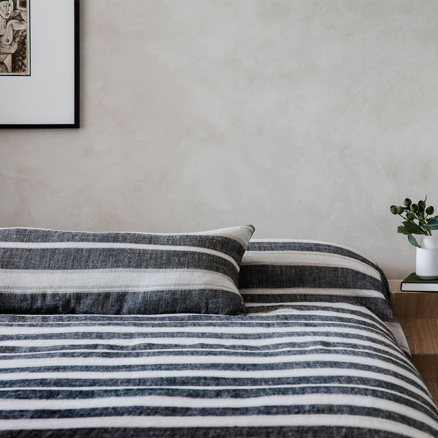 Mira Lumbar Cushion Cover and Bedcover in Enzo styled on a bed.