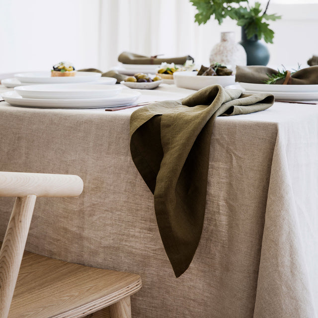 A close up on the Linen Table Napkin in Olive draped over the edge of a table styled with the Linen Tablecloth in Natural. There is white crockery on the table.