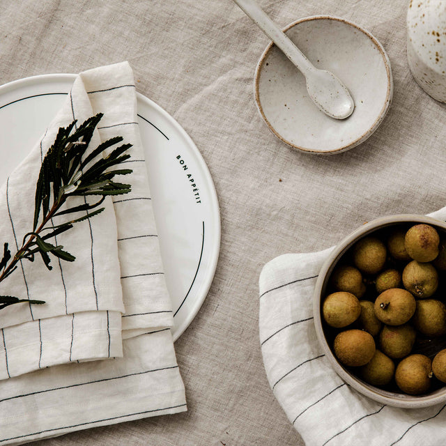 A table setting of the Linen Tablecloth in Natural, Linen Table Napkins in Pencil Stripe, a ceramic bowl, plate and spoon, and longan fruit.
