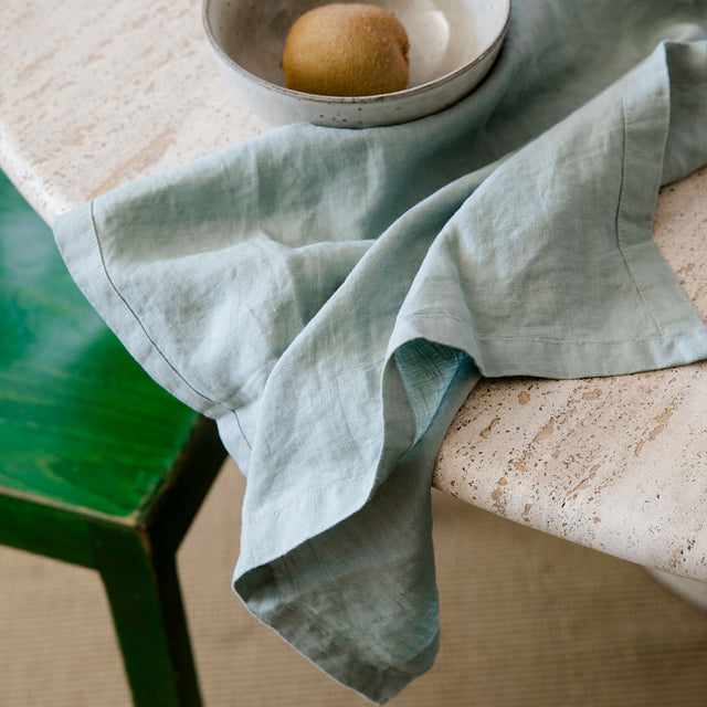 A Sage Linen Table Napkin hanging over the edge of a stone table. On top of the napkin is a bowl containing a kiwi fruit.
