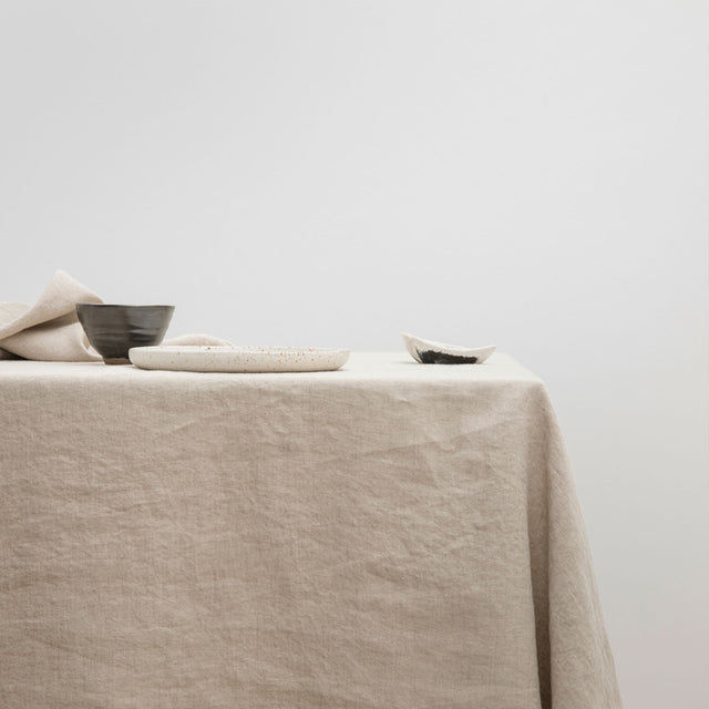 The Linen Tablecloth in Natural styled with various ceramic objects.