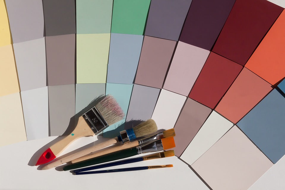 A selection of different colours on paper alongside paint brushes