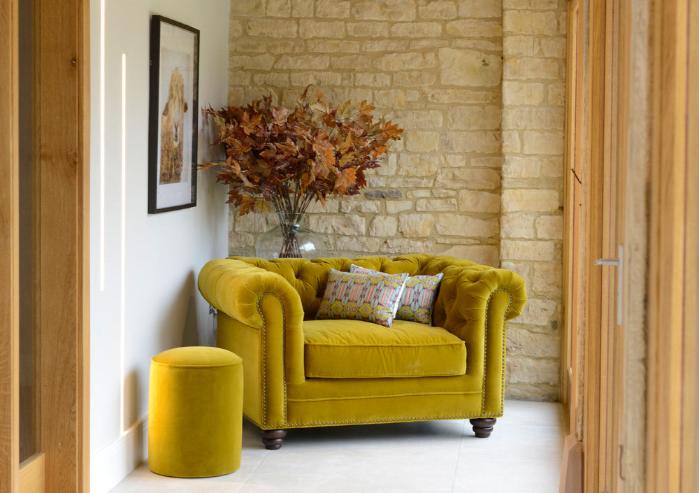 A mustard yellow chair in a light an airy room.