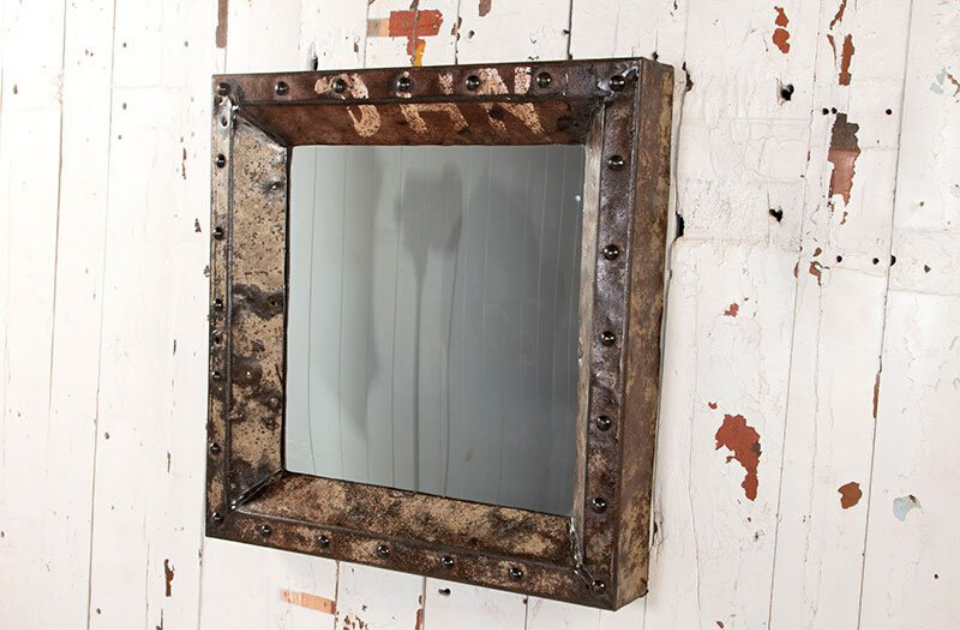 An iron-studded mirror hanging on a distressed white painted wall.