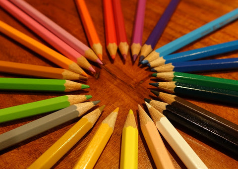 Pencils forming a colour wheel on a wooden surface