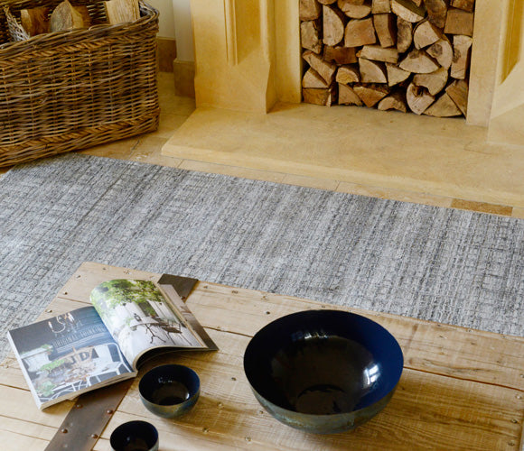 A Cotswold Grey rug in front of a fireplace.