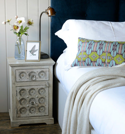 Jali bedside cabinet next to comfortable bed in Cotswold Grey apartment