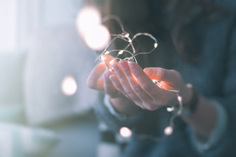 A woman holding fairy lights in her hand.