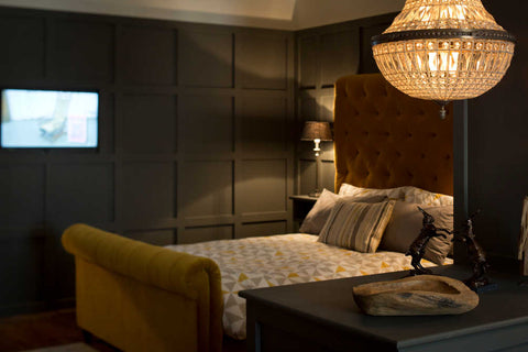 A modern bedroom with yellow bed and dark walls by Cotswold Grey