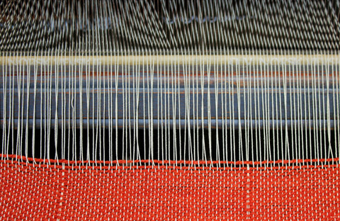 Fabric being created using a loom