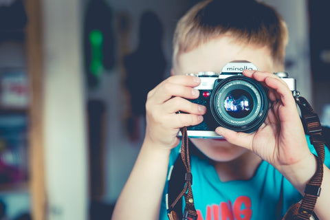 A young boy holding a camera and taking a picture.