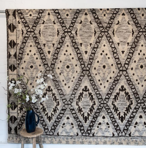 A Moroccan style rug hanging on a wall.