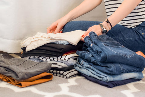 A woman folding clothes and putting them into piles.