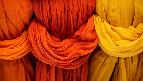 Three orange and yellow coloured scarfs hanging.