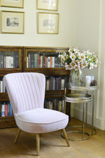 The wooden legs of the blush pink Cotswold Grey occasional chair.