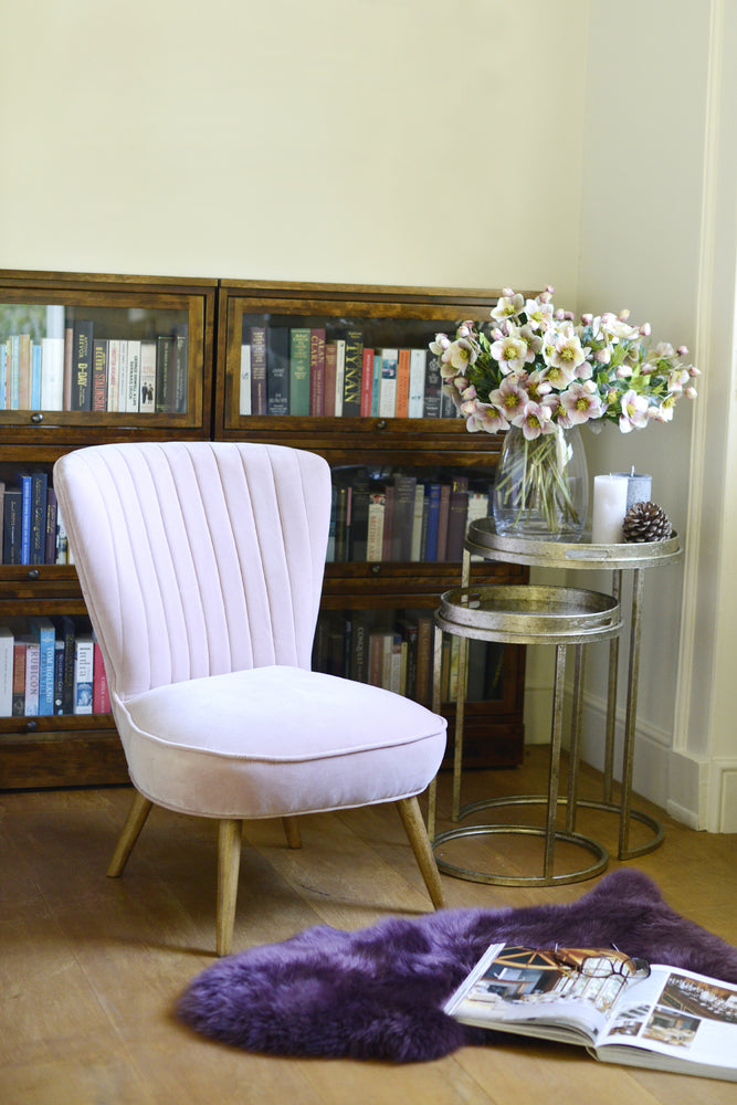 Classic blush pink velvet covered occasional chair in sophisticated reading room.