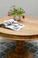 Round wooden base table complimented by a flowerpot and an open book