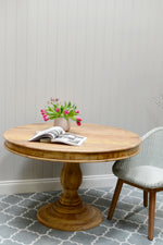 Round base wooden dining table in a light brown / beige colour complimented by the grey woven chair