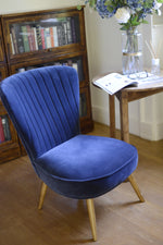 The sumptuous navy blue fabric covering deep luxurious padding with hardwood legs on the Cotswold Grey Pearson Chair.