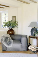 Cool grey leather chair, dressed with grey sheepskin in room.