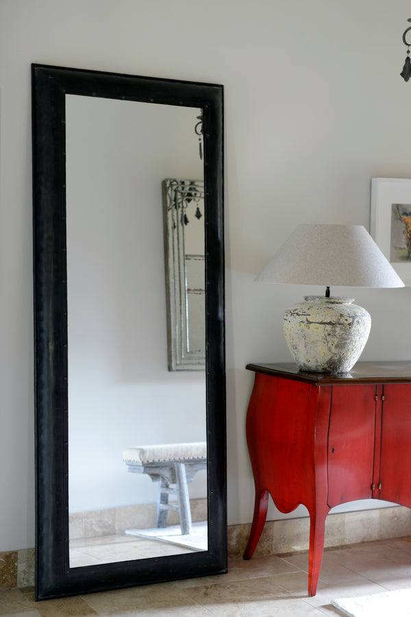 Large black iron rectangular mirror in a lifestyle shot stood next to a red chest