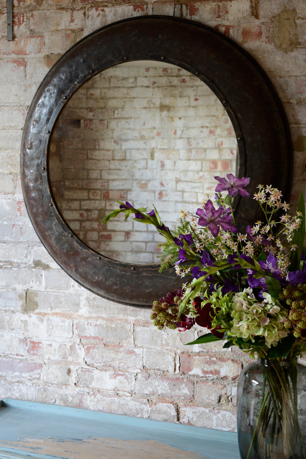 Large mirror hung on exposed brick wall next to flowers in vase