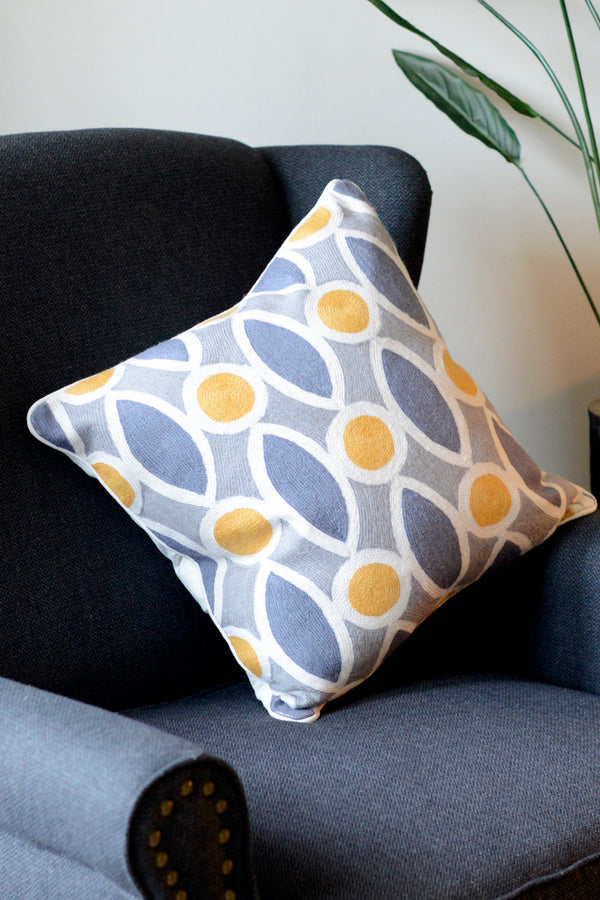 Halo patterned cushion sitting on its corner on a chair