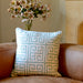 Pale blue patterned cushion on brown leather sofa