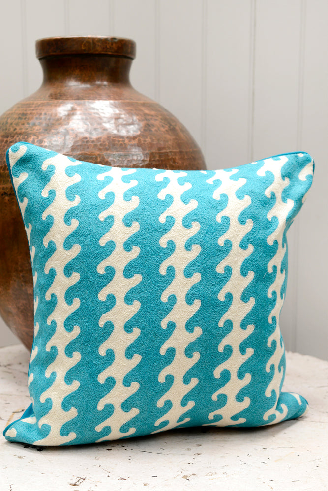 Blue patterned cushion leaning against the brass pot