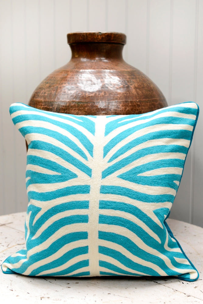 Light blue patterned cushion leaning agains the brass pot