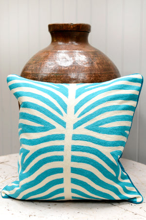 Load image into Gallery viewer, Light blue patterned cushion leaning agains the brass pot