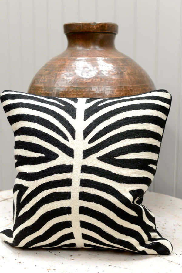 Black and white patterned cushion leaning against a brass pot