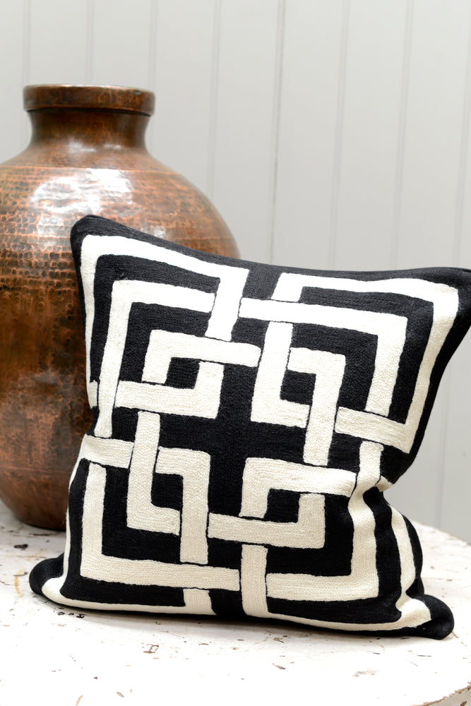 Black and white patterned cushion leaning on the brass pot