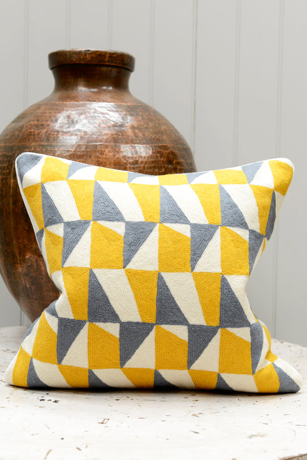 Blue and yellow patterned cushion leaning against a brass pot