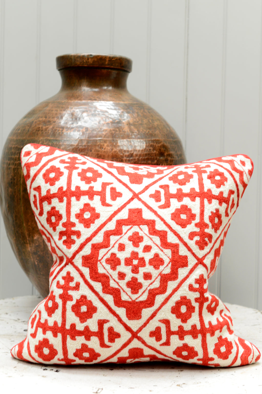 Red patterned cushion leaning on a brass pot