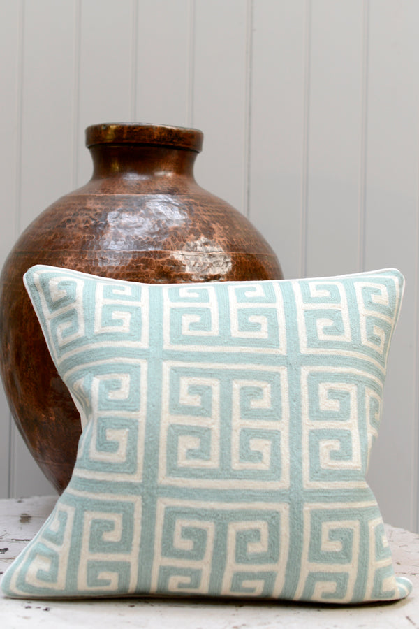 Pale blue patterned square cushion leaning against a brass pot
