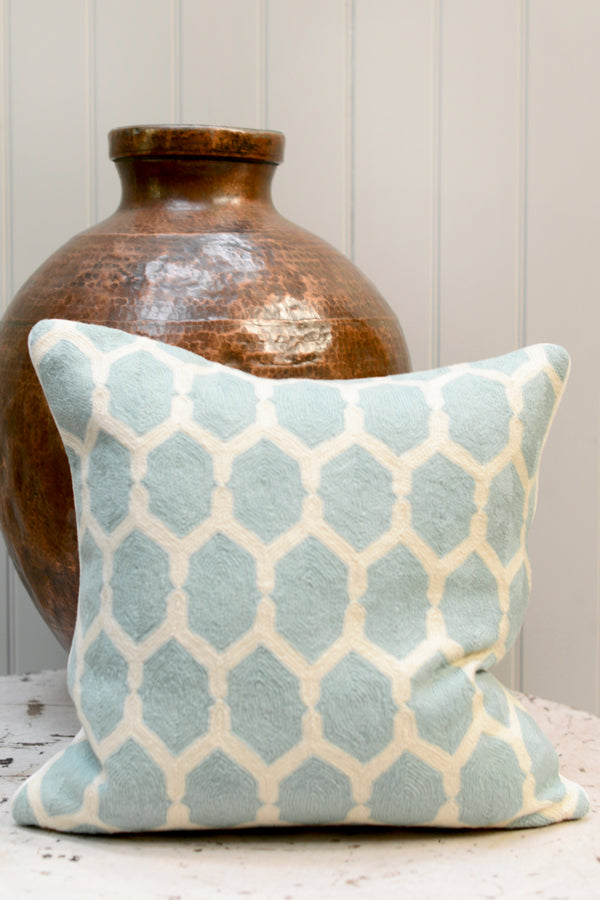 Pale blue patterned cushion leaning against a brass pot