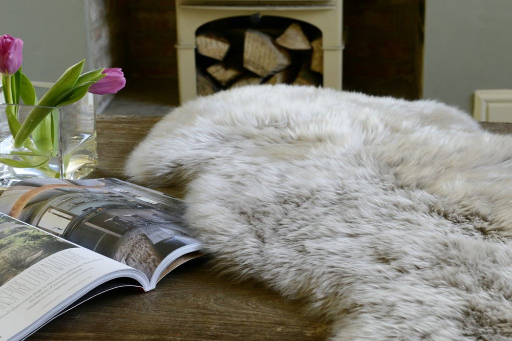 White soft sheepskin rug pictured next to an open book next to the fireplace