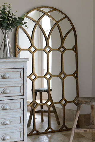 Antique gold coloured framed mirror, lining against a wall.