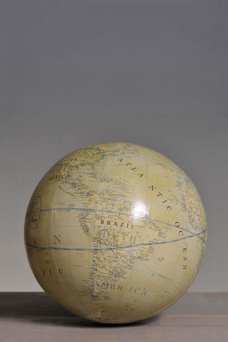 Free standing 'vintage' globe resting on a table top.