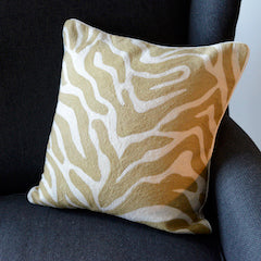 Beige patterned cushion sat on an arm chair