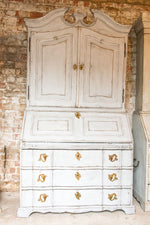 A solid oak white bureau with a worn, rustic look stood against a brick wall