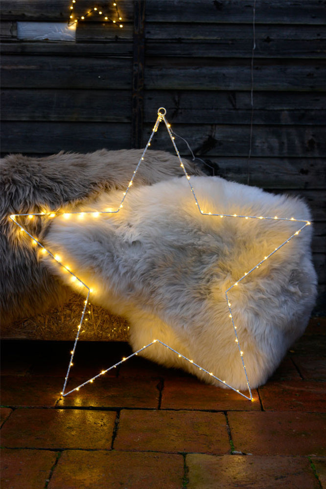 A white 80L Liva star frame with fairy lights on to leant against a fur throw.