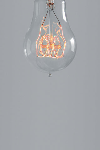 Nostalgia Quad Loop Light Bulb pictured turned on and hanging in a studio