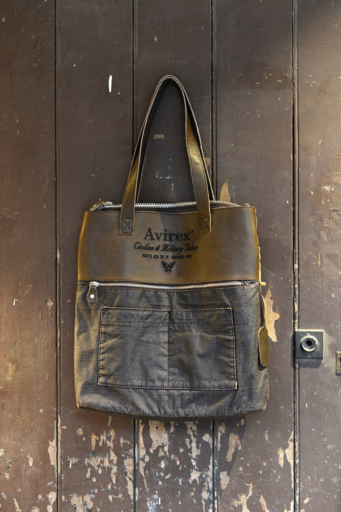 Avirex D-Day vintage look leather brown Shopping bag, hanging on brown wooden door.