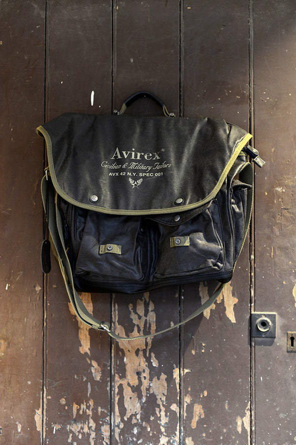 Vintage looking leather Avirex Alifax Briefcase bag hanging on brown door.
